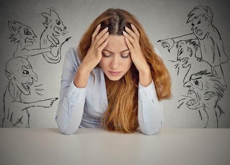 las emociones: Hombres malvados apuntando a mujer estresada. Desesperada empresaria joven sentado en el escritorio en su oficina aislada en el fondo de la pared gris. Emociones humanas negativas enfrentan sentimientos de expresión percepción vida