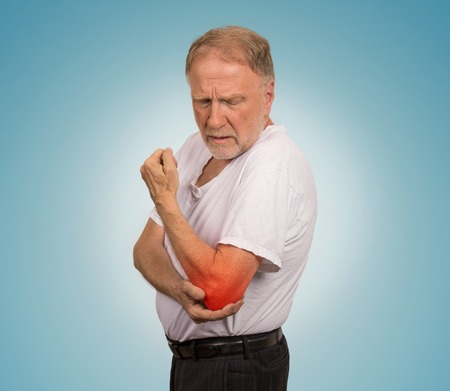 rheumatism: Closeup senior man with elbow inflammation colored in red suffering from pain and rheumatism isolated on light blue background with copy space Stock Photo