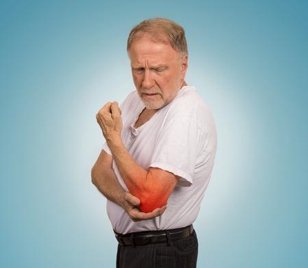 codo: Hombre mayor del primer con la inflamación del codo de color rojo en el sufrimiento del dolor y el reumatismo aislado en fondo azul claro con espacio de copia Foto de archivo