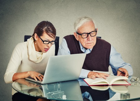 Portret jonge vrouw die op laptop werkt en ouder senior volwassen opa man het lezen van boek op tafel geïsoleerd grijze muur achtergrond. Generatie verschillen en gap technologisch concept