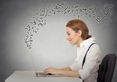 Side profile business woman sitting at desk in her office working on a laptop computer, typing with alphabet letters flying up Stock Photo