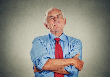 exasperation: Portrait of unhappy grumpy pissed off senior mature man isolated on gray wall background. Negative human emotions, face expression feelings