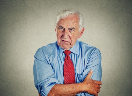 Portrait of unhappy grumpy pissed off senior mature man isolated on gray wall background. Negative human emotions, face expression feelings