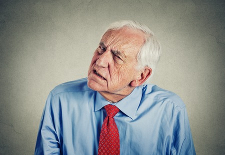 Closeup portrait headshot senior man hard of hearing asking someone to speak up can't hear isolated gray wall background. Archivio Fotografico