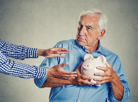 piggies: Closeup portrait senior man grandfather holding piggy bank looking suspicious trying to protect his savings from being stolen isolated on gray wall background. Financial fraud concept Stock Photo