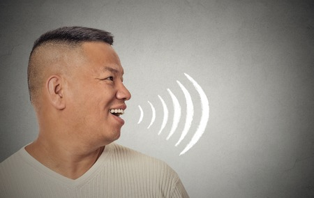 Side profile portrait young man talking with sound waves coming out of his open mouth isolated grey wall background. Human face expressions