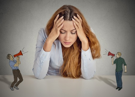 Desperate unhappy young business woman leaning on a desk two men with megaphone screaming at her isolated grey wall office background. negative human emotions face expression feelings life perception