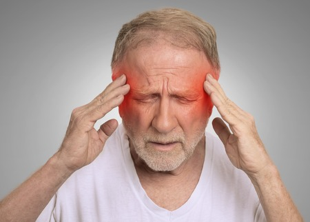 expression: Closeup headshot senior man suffering from headache hands on head with red colored inflamed areas looking down isolated on gray wall background. Human face expression. Health problems issues