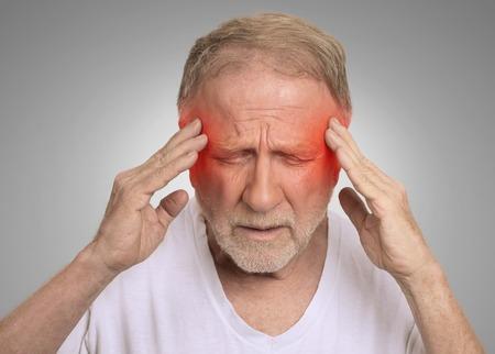 dolor de cabeza: Primer hombre mayor tiro en la cabeza que sufren de dolor de cabeza las manos en la cabeza con las áreas inflamadas de color rojo mirando hacia abajo aislado en el fondo de la pared gris. Expresión de la cara humana. Problemas de salud temas