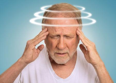 Headshot senior man with vertigo. Elderly male patient suffering from dizziness isolated on light blue background Stockfoto