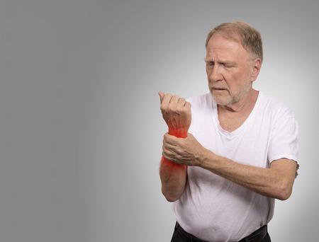 Lijden aan pijn en reuma. Closeup ouderen, senior oude man kijkt ongelukkig in grote ondraaglijke de hand pijn pijnlijke pols gekleurd in het rood geïsoleerd op een grijze achtergrond. Gezondheid geeft problemen Stockfoto