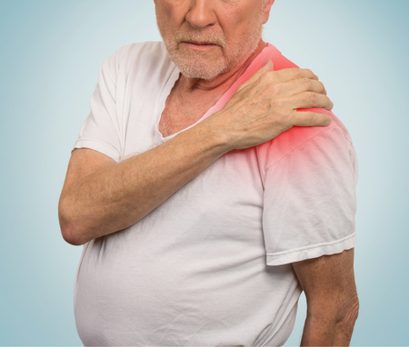 cuff: senior man with pain in his shoulder isolated on light blue background Stock Photo
