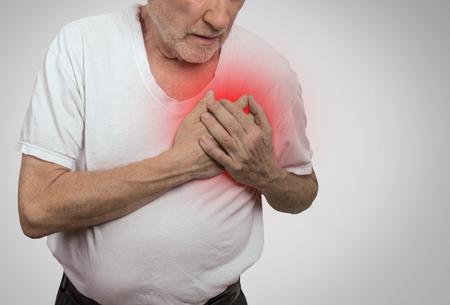 seniors suffering painful illness: senior man suffering from bad pain in his chest isolated on gray background Stock Photo