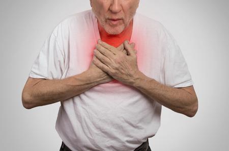 Close-up portret zieke oude man, bejaarde man, die ernstige infectie, pijn op de borst, op zoek ongelukkig onwel, probeert te vangen zijn adem die op grijze achtergrond. Geriatrische zorgconcept