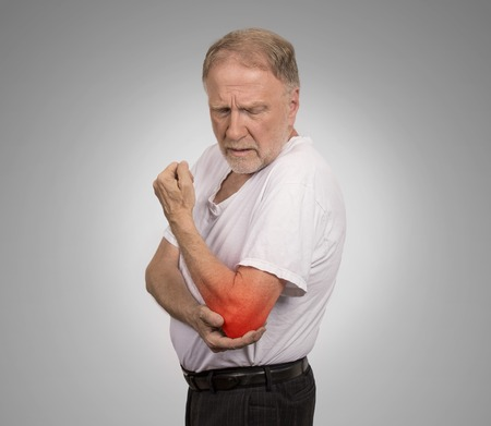 Closeup senior man with elbow inflammation colored in red suffering from pain and rheumatism isolated on gray wall background with copy space Stock Photo