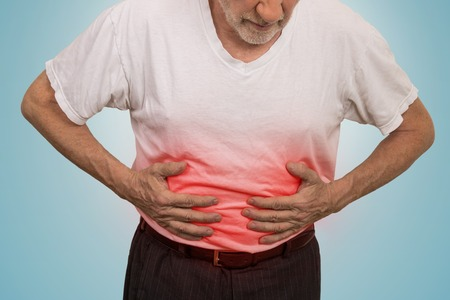 inflammatory bowel diseases: Stomach ache, man placing hands on the abdomen isolated on light blue background Stock Photo