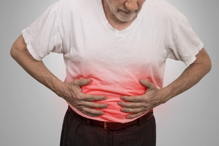 bowel: Stomach ache, man placing hands on the abdomen isolated on gray wall background
