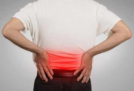 dolor de espalda: vista trasera anciano abuelo holding su dolorosa baja de la espalda de color en rojo con las manos aisladas en fondo gris. Problemas de salud humana