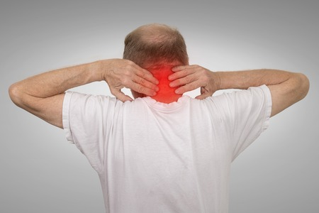 geriatrics: Closeup senior mature man with bad neck spasm pain touching colored in red inflamed area suffering from arthritis isolated on gray wall background. Human health problems, geriatrics medicine concept