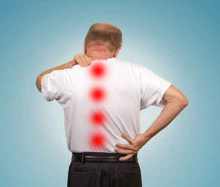 impingement: Senior elderly man with backache isolated on light blue background. Health care patient concept Stock Photo