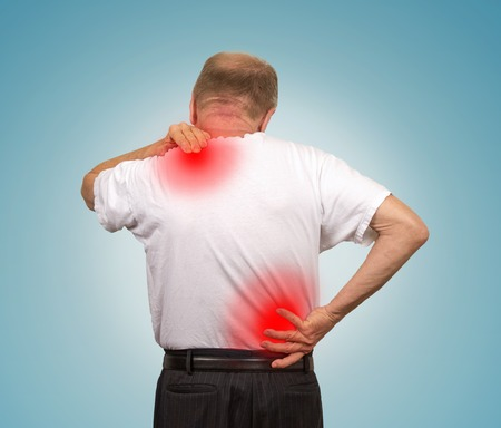 chiropractic: Senior elderly man with lower and upper back pain isolated on light blue background. Spinal cord problems