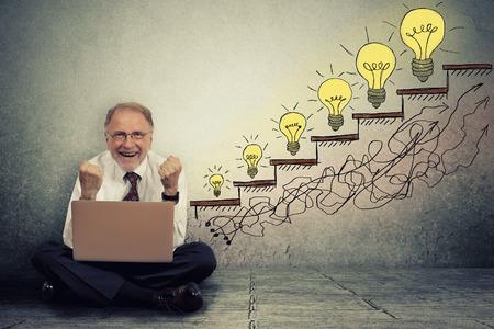 growth: Hombre ejecutivo feliz emocionado senior, trabajando en equipo, sentado en un piso en su oficina celebra el �xito del negocio, promoci�n, crecimiento de la empresa aislada en la pared gris de textura de fondo