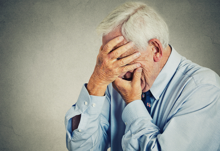 isolated on gray: Closeup portrait sad depressed, stressed, thoughtful, senior, old man, gloomy, worried, covering his face isolated gray wall background. Human face expressions, emotion, feelings, reaction, attitude