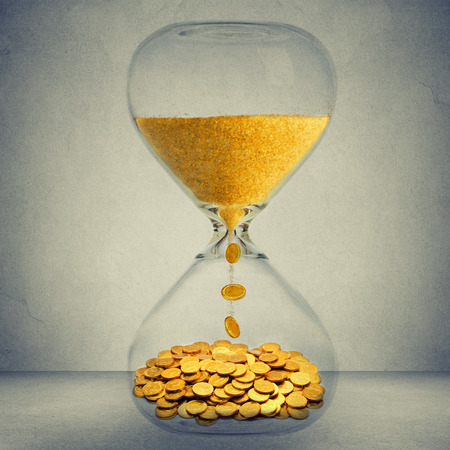 sand timer: Time is money financial opportunity concept. Sand clock with gold dust and coins isolated on gray wall background
