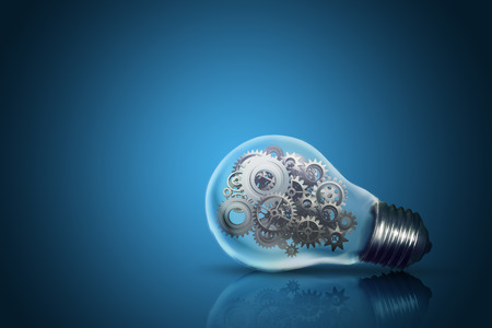 Close up of light bulb with gear mechanism inside isolated on dark blue background