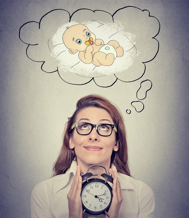 anticipating: Portrait happy woman anticipating a baby looking up holding alarm clock isolated on gray wall background. Positive face expression emotion Stock Photo