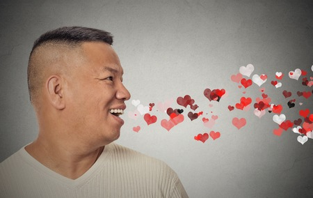 mouth kiss mouth: Side view portrait man sending kisses, red hearts coming out of open mouth, isolated grey wall background. Positive emotions, facial expression. Valentines day
