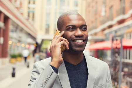 Portrait young urban professional smiling man using smart phone photo