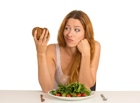 Young woman tired of diet restrictions deciding whether to eat healthy food or sweet cookies she is craving sitting at table isolated white background. Human face expression emotion. Nutrition concept