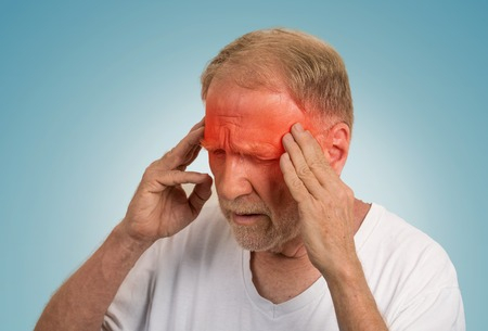 geriatrics: Closeup headshot senior man suffering from headache hands on head with red colored inflamed areas looking down isolated on light blue background. Human face expression. Health problems issues