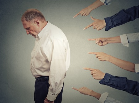 Concept of accusation guilty businessman person. Side profile upset old man looking down many fingers pointing at him isolated grey office wall background. Human face expression emotion feeling