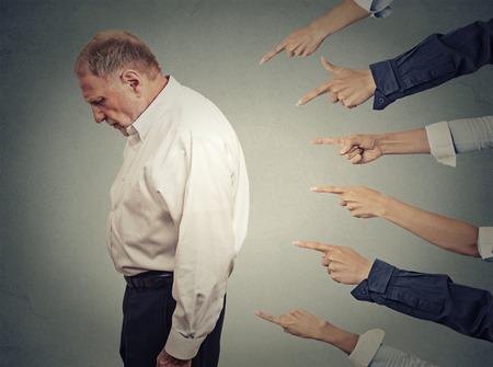 Concept van de aanklacht schuldig zakenman persoon. Zijprofiel boos oude man naar beneden vele vingers wijzen naar hem geïsoleerde grijze kantoor muur achtergrond. Menselijk gezicht meningsuiting emotie gevoel