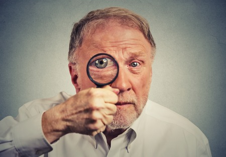 degeneration: Closeup surprised man looking through a magnifying glass