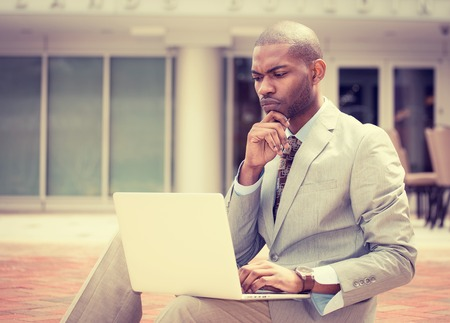 african american man: Serious business man working on laptop computer outdoors Stock Photo