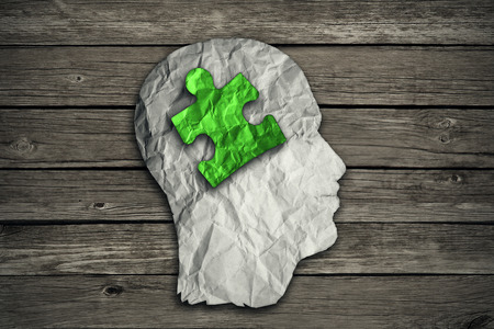 Puzzle head solution concept as a human face profile made from crumpled white paper with a jigsaw piece cut out inside the brain area on old wood background. Mental health symbol.