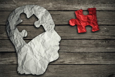 contemplate: Puzzle head brain concept as a human face profile made from crumpled white paper with a jigsaw piece cut out on a rustic old wood background as a mental health symbol. Stock Photo