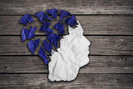 losing memory: Alzheimer patient medical mental health care concept as a sheet of torn crumpled white blue paper shaped as side profile of human face on wood as a symbol for neurology and dementia or memory loss.