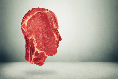 health decisions: Food balance health related eating choices. Red steak meat shaped as human head. Nutritional decisions and diet concept