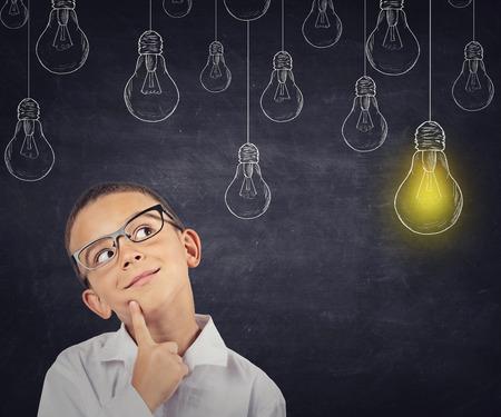 bambini pensierosi: Grande idea. Ragazzo intelligente con soluzione lampadina sopra la testa