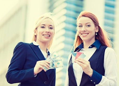 Closeup portrait happy smiling young businesswomen with credit cards and cash on hands, convenience of electronic money isolated corporate office background. Financial decision, banking system concept