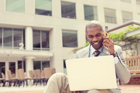 ejecutivo en oficina: Hombre de negocios joven hermoso que trabaja con la computadora port�til al aire libre hablando por tel�fono m�vil. Foto de archivo