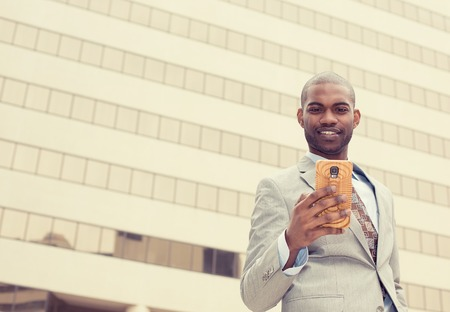 american media: Closeup portrait, happy, cheerful man excited by what he sees on cell phone, isolated outdoor background corporate office. Facial expression, reaction. Businessman sending text message from his mobile