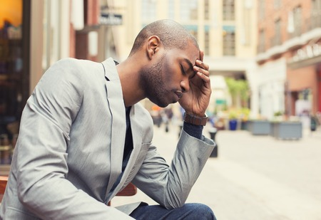 Portrait stressed young man hands on head with bad headache isolated city street background. Negative human emotion facial expression feeling Stockfoto