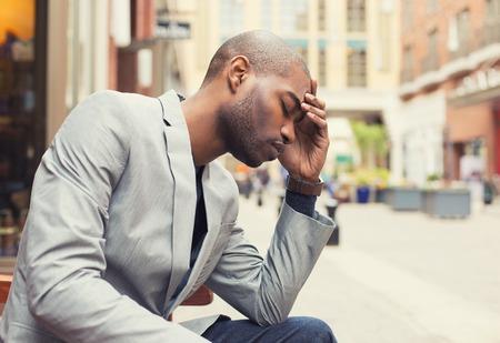 depresi�n: Retrato subray� hombre joven manos en la cabeza con dolor de cabeza aislado fondo calle de la ciudad. Emoci�n humana Negativo sentimiento expresi�n facial