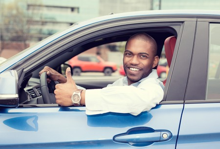 drives: Car side window. Man driver happy smiling showing thumbs up driving sport blue car isolated outside parking lot background. Handsome young man excited about his new vehicle. Positive face expression Stock Photo