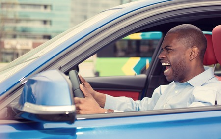 pissed off: Closeup portrait displeased angry pissed off aggressive young man driving car shouting at someone isolated traffic background. Emotional intelligence concept. Negative human face expression Stock Photo